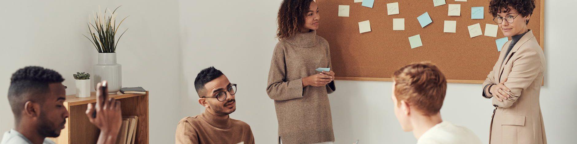 two women standing beside brown board on wall